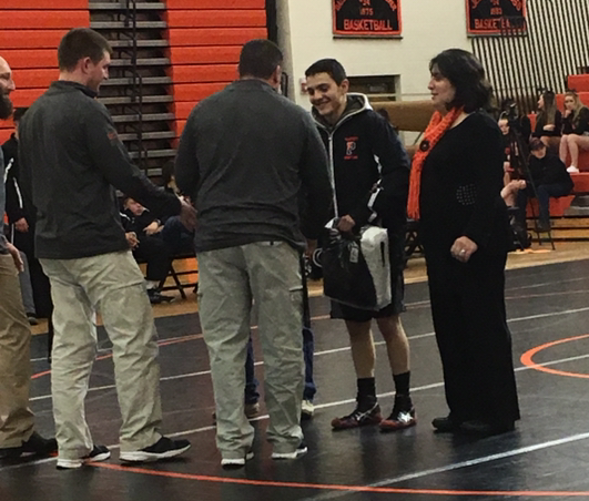 Senior Brian Brazelton (center) is congratulated by coach Nick Fulton (far left) and Nate Urbach and Brian's mother Lillian Brazelton on Senior Night.