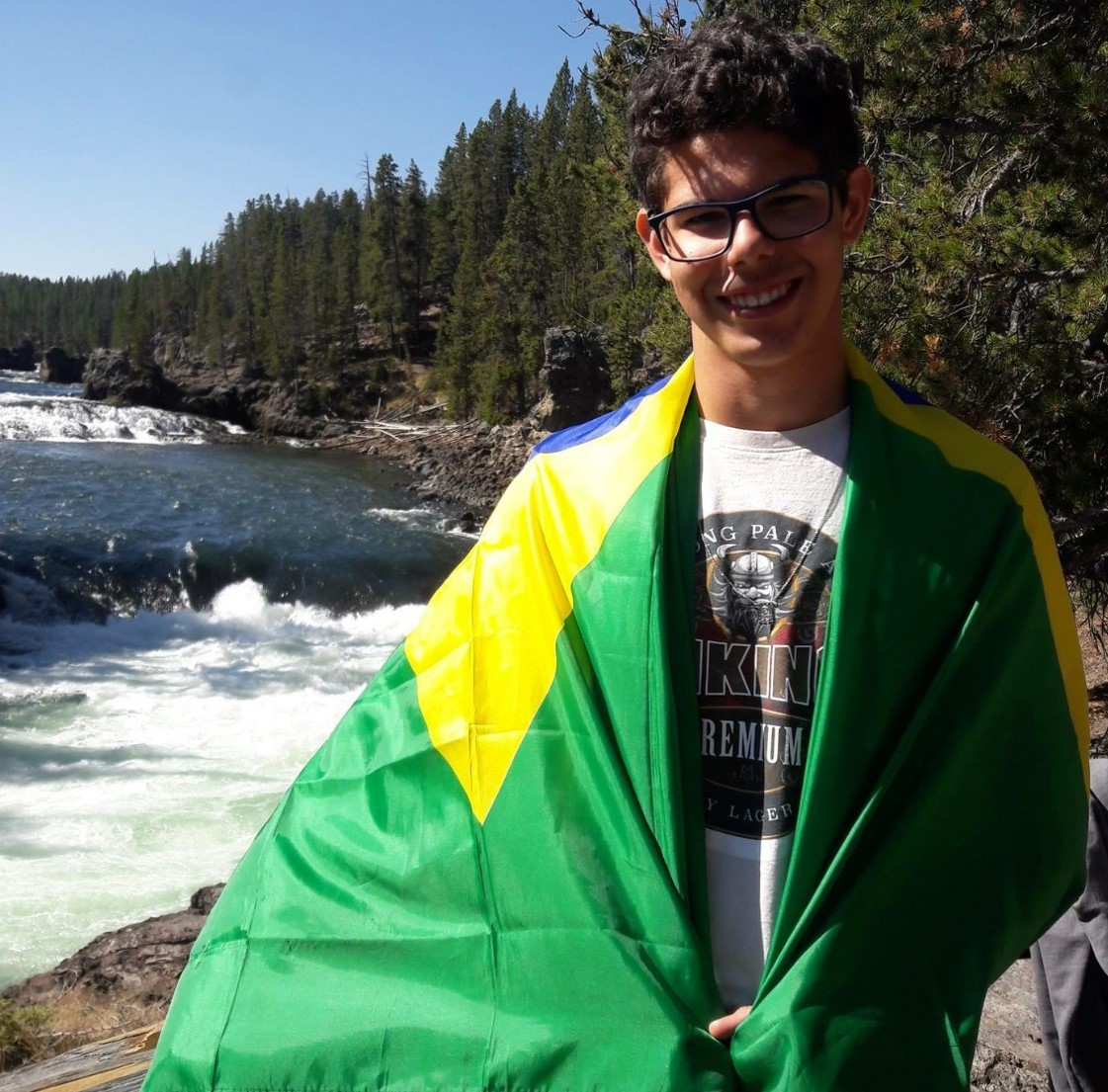 Pedro Teixeira poses for a picture with the Brazilian flag wrapped around him in Yellowstone National Park.