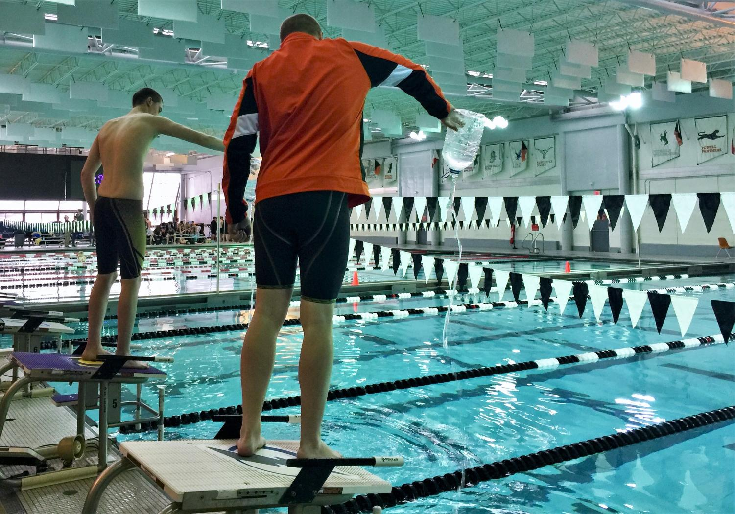 Seniors Joe Rogers (front) and Trenton Wilson pour the Powell Aquatic Center's pool water into Gillette's lanes, an ongoing tradition which takes place at the Wyoming State 3A Championships.
