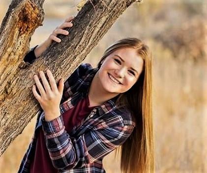 Ashtyn Heny leans against a tree.
