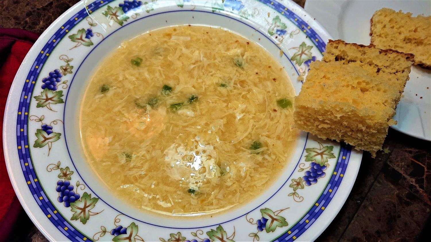 Warm bowl of egg drop soup with a side of cornbread.