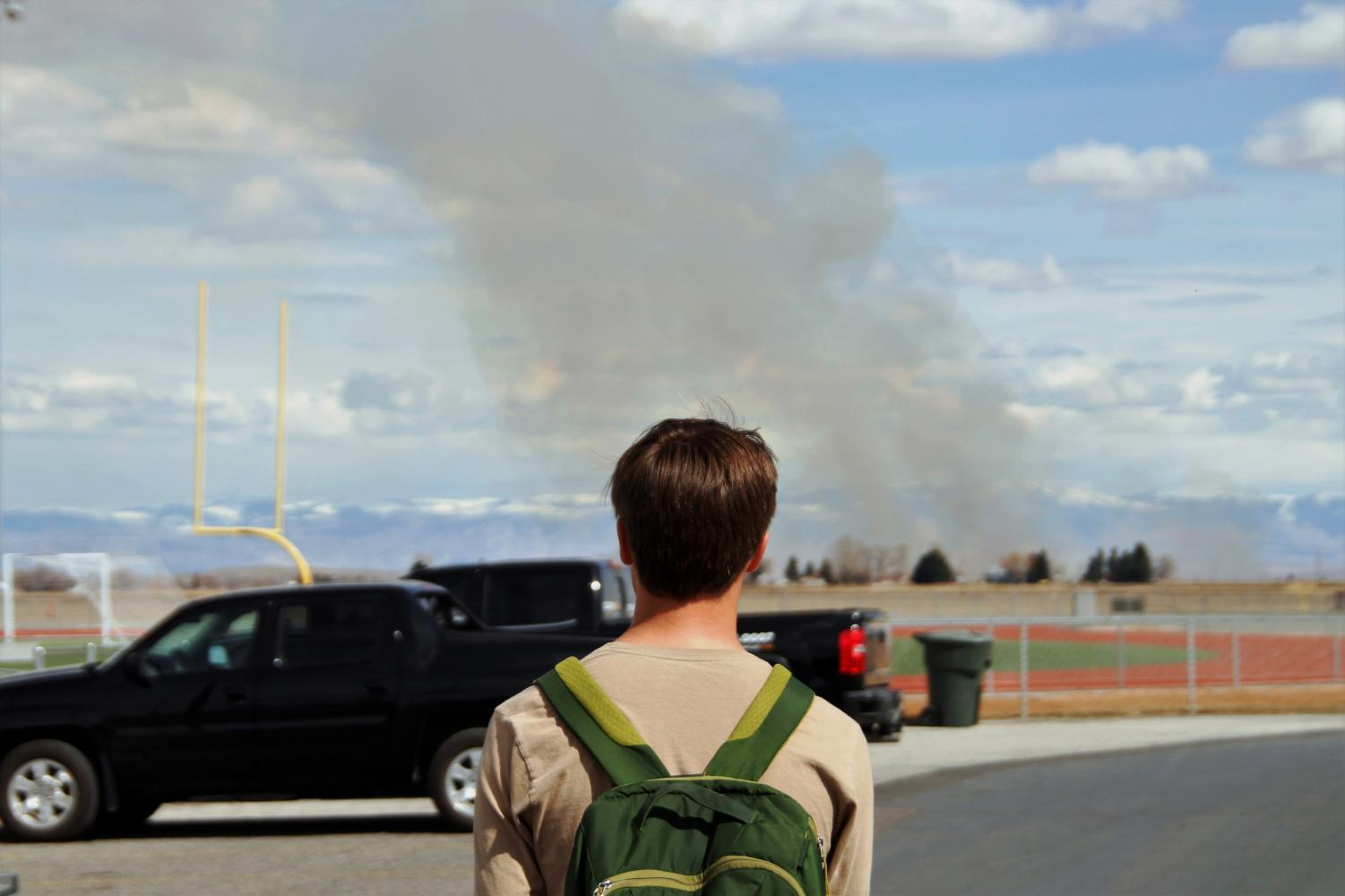 Freshman Jace Bohlman looks at Powell High School's track as smoke from a nearby burning field rises above it.
