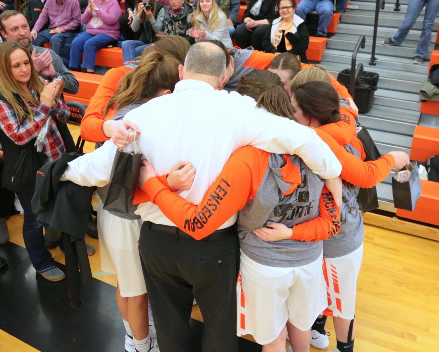 The Lady Panther basketball team has a group hug with Coach Mac on their senior night earlier in the season