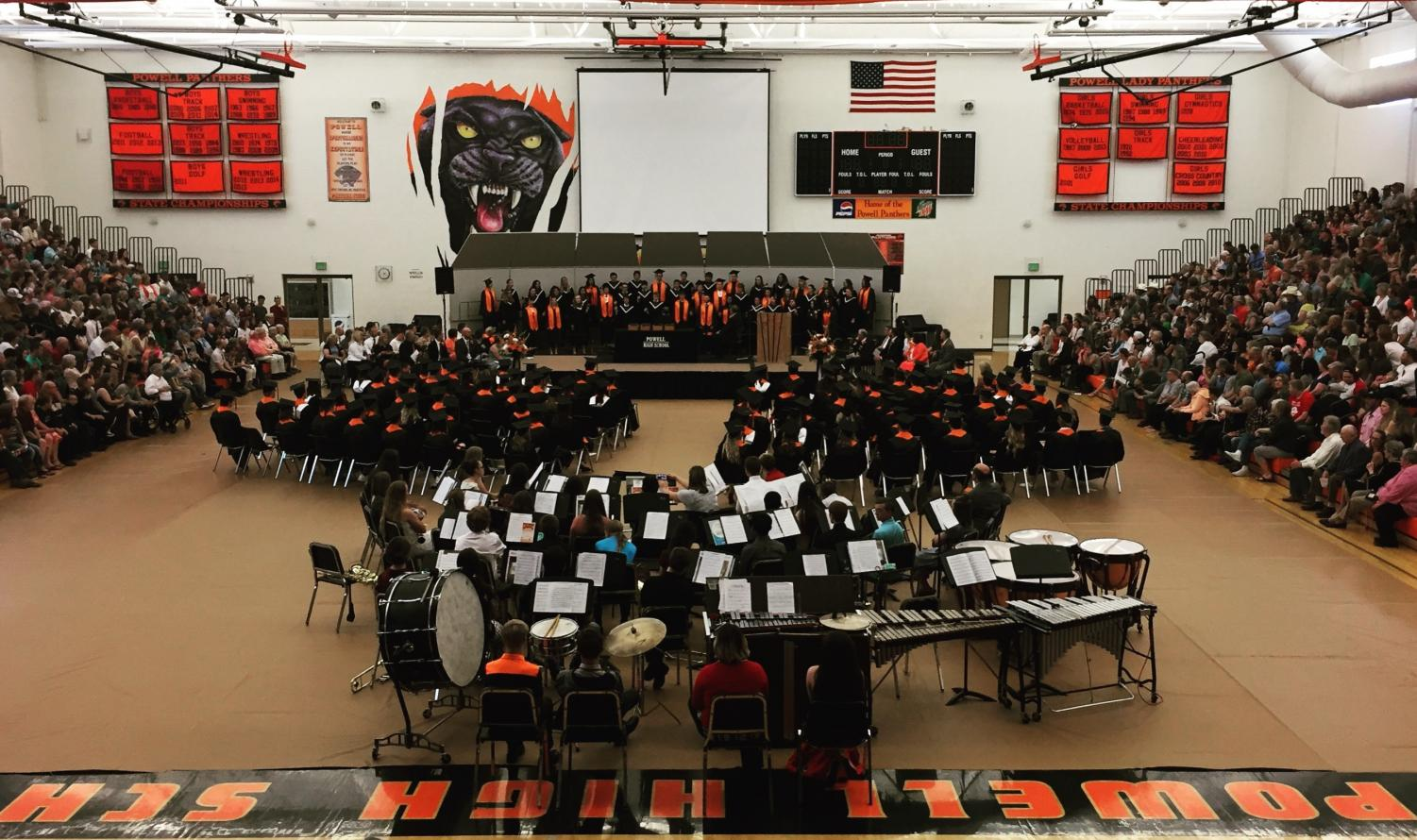The graduating class of 2018 and audience give their attention to the Powell High School choir.