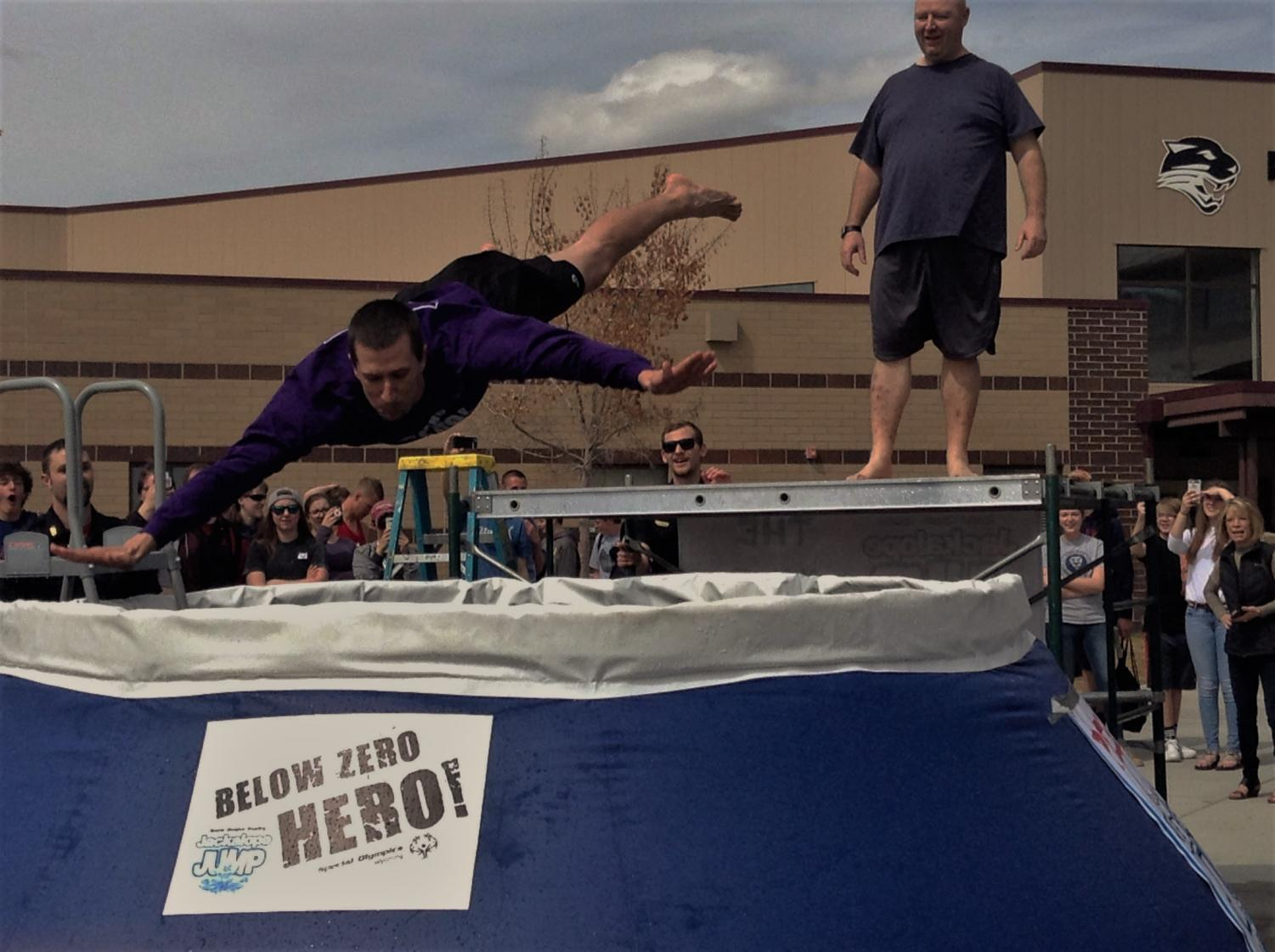 Mr. Preator dives into the pool outside of Powell High School