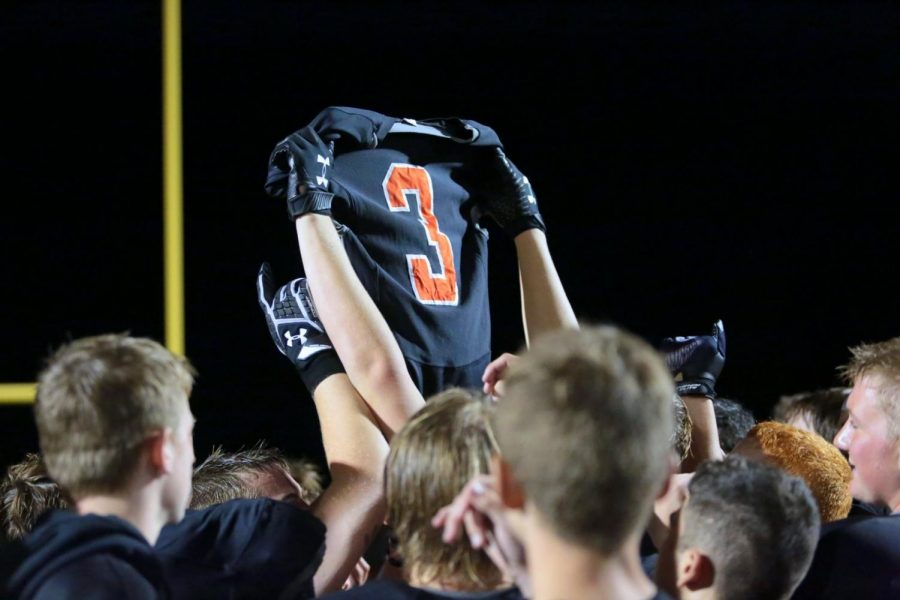 The+Panther+football+team+hoists+Ethan+Asher%E2%80%99s+jersey+in+the+air+during+the+game+Friday+night+against+Worland.