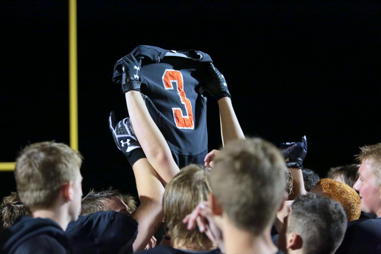 The Panther football team hoists Ethan Asher's jersey in the air during the game Friday night against Worland.