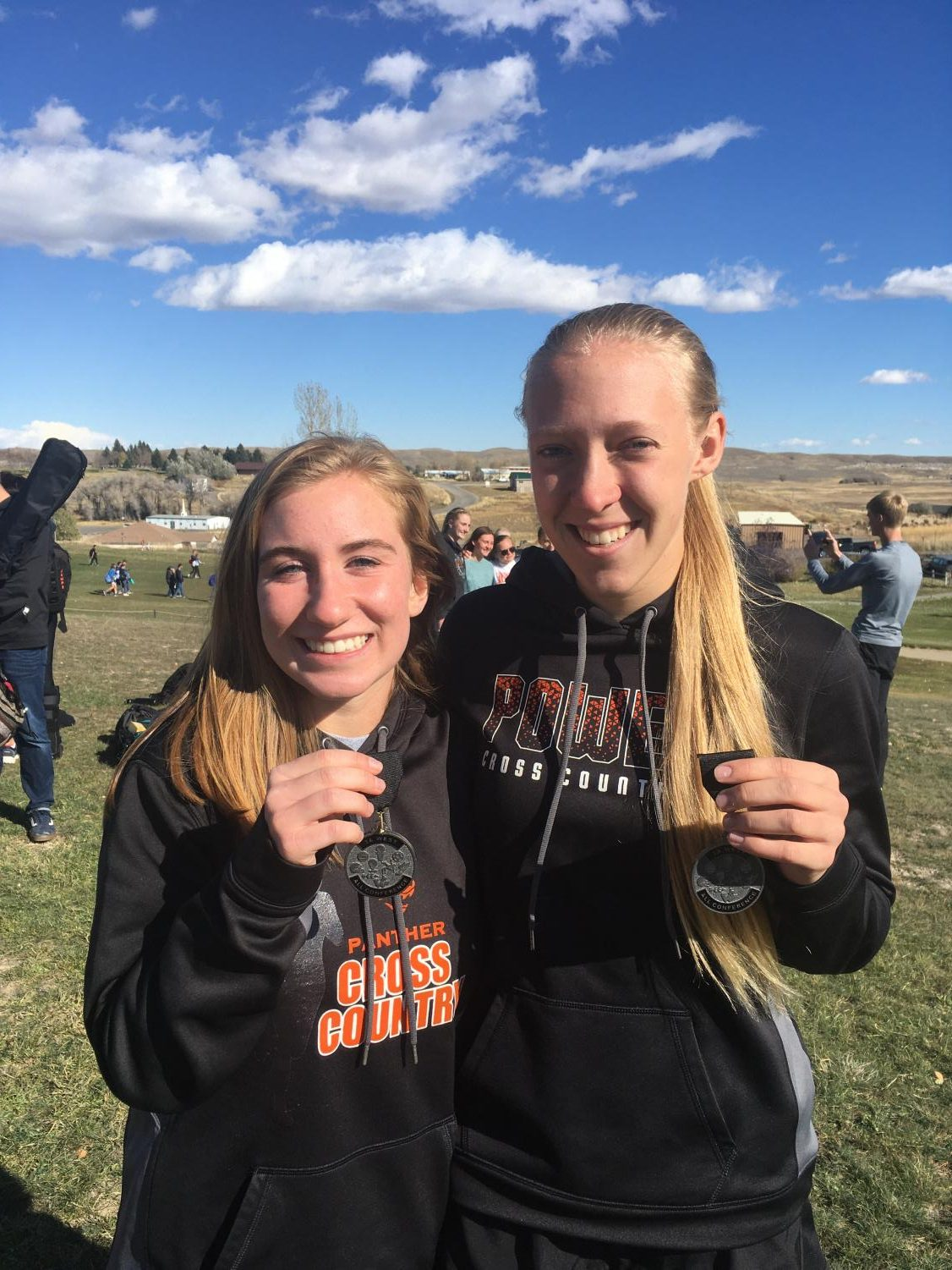 Senior Kayla Kolpitcke and sophomore Kabrie Cannon pose with their All-Conference medals after the conference cross country meet in Lander. All-Conference is awarded to the top ten runners in each conference.