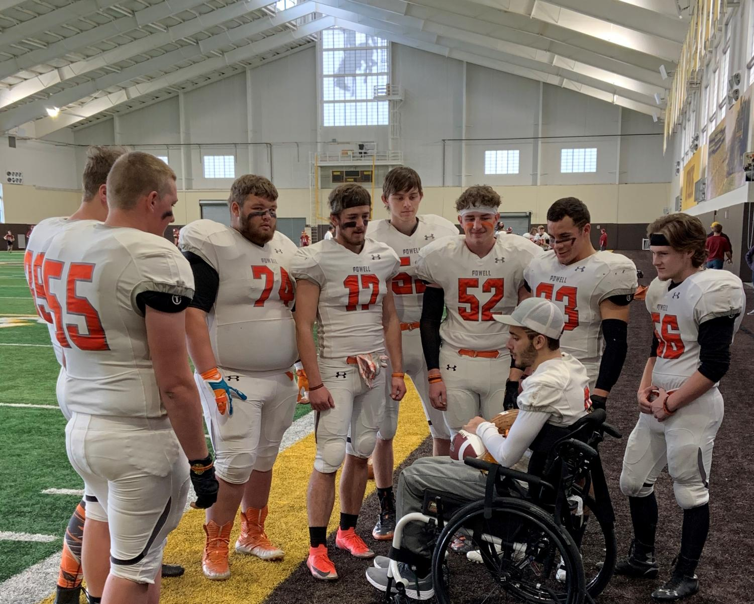 The PHS football seniors gather around injured teammate Ethan Asher after being reunited with him for the first time since Asher's accident.