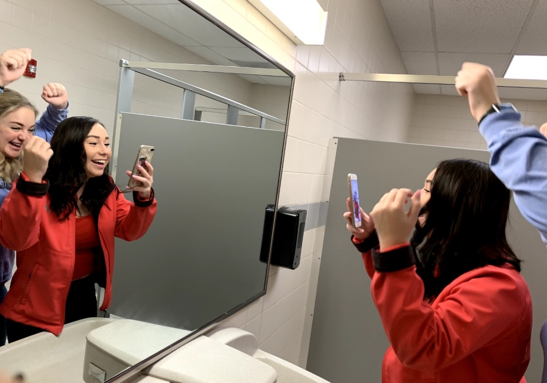 Seniors Tenna Desjarlais and Taeli Hessenthaler film a Tik Tok in the school bathroom.