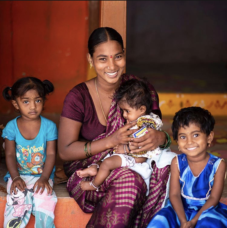 A+woman%2C+helped+by+Rescue+Pink%2C+sits+for+a+picture+with+her+three+daughters.%0A%0A