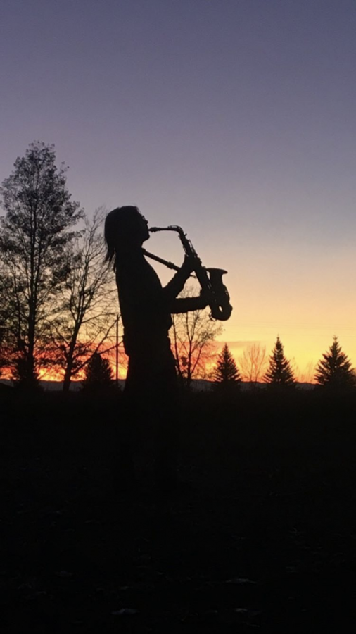 Sophomore+Aiden+Chandler%2C+a+PHS+jazz+band+mdmber%2C+plays+his+alto+saxophone+with+a+sunset+backdrop.