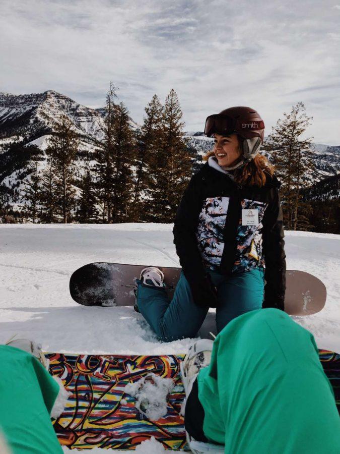 PHS junior Elsie Spomer looks down the ski slope while taking a quick break from snowboarding.