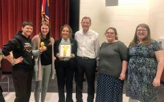 (from left to right) Makenna Alley, Anna Atkinson, Elsie Spomer, senator John Barrasso, Crystal Emmett and Hannah Hawley posing with team mascot, Gustavo, in the Riverton High School auditorium.