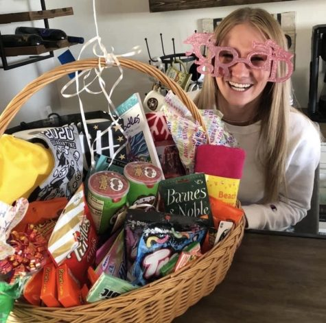 "Senior Skylar Cooley poses with the gift basket she received from her newly ""adopted"" parents."