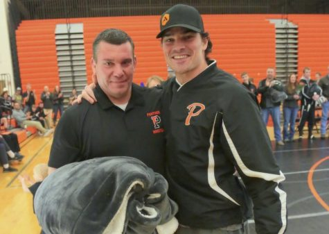 Former Panther wrestler Olie Olsen (right) was on hand to surprise Mr. Nate Urbach and present him with a retirement blanket during Urbach's final meet in the Panther Gym in February.