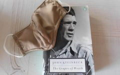 """John Steinbeck's """"Grapes of Wrath,"""" a novel about the Great Depression, with a face mask worn to prevent the spread of COVID-19."""