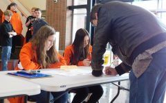 Sophomore Camryn Patton and senior Lauren Dewitz work the check-in table at Powell High School's speech tournament last year.
