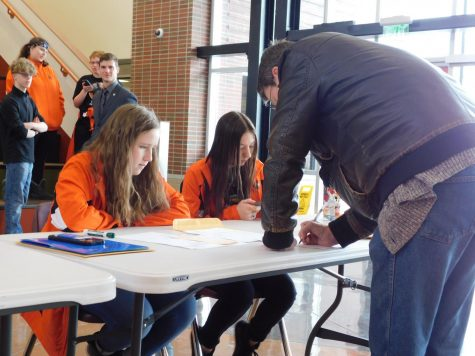 Sophomore Camryn Patton and senior Lauren Dewitz work the check-in table at Powell High School