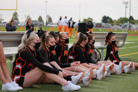The Powell High School Cheerleading Team wears their masks while sitting on the sidelines.