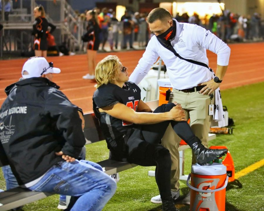 Alan Hill, athletic trainer at PHS, and William Jarvis,Powell Valley's Orthopedic Surgery Doctor, talks with Riley Bennett after he breaks his pelvis at the Bighorn brawl, which took place on September 25th.