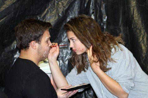 PHS senior Elsie Spomer works on senior Jaxton Braten's face paint for the haunted house.