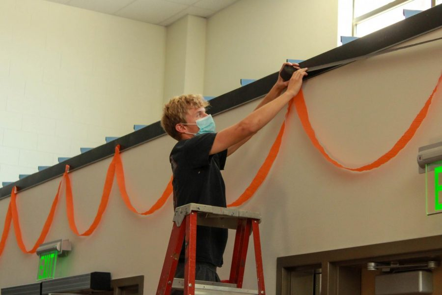 PHS junior Keaton Rowton hangs streamers over the entryway in the commons for Homecoming week in September. Student Council focused on decorations and dress-up days during 2020 Homecoming due to the lack of events taking place because of COVID-19.