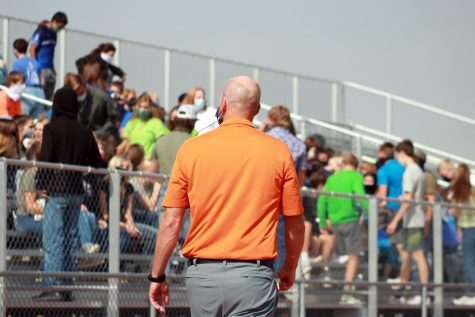 Powell High School Principal Mr. Tim Wormald walks past students gathering on the bleachers for an assembly.