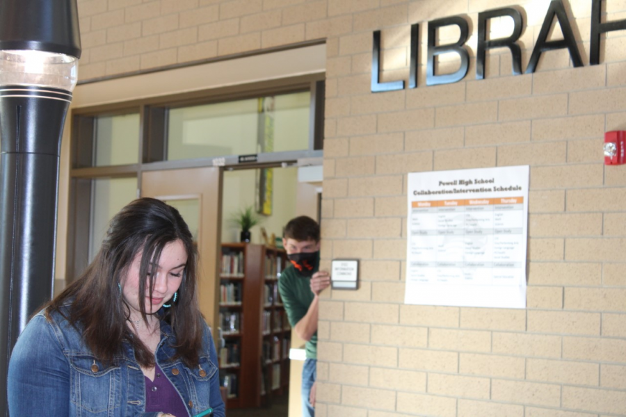 (Prowl Photo Illustration) PHS sophomore Lilly Morrison walks by the library while PHS sophomore Austin Graft creeps nearby.