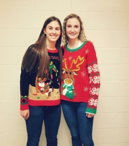 In the PHS locker room, sophomore Megan Jacobsen (left) and senior Hailee Hyde show off their hot Christmas sweaters.