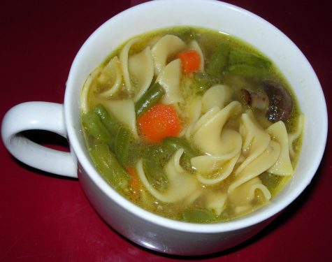 A perfectly sized mug of chicken noodle soup mixed with carrots, celery, mushrooms and fresh chopped parsley.
