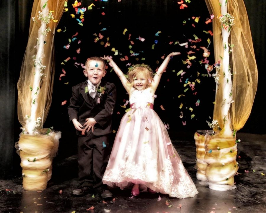 Mr. Nick Fulton's son, Fisher Fulton, and Mrs. Charli Fluty's daughter, Graelyn Fluty, throw confetti into the air during the grand march of Powell High School's 2019 Prom.