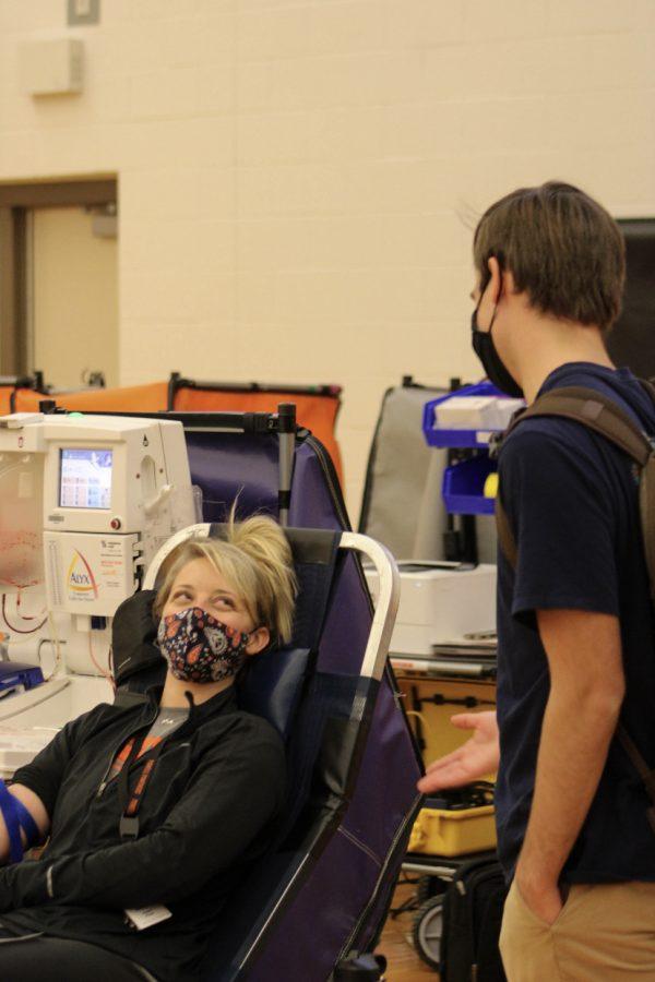 P.E. teacher Mrs. Charli Fluty gets her blood drawn while junior Jace Bohlman talks to her.