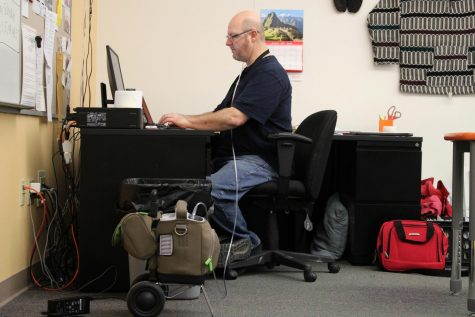 PHS English and Spanish teacher Mr. Hans Hawley works at his desk at school. Beside him is his oxygen tank, which he requires after recovering from COVID-19.
