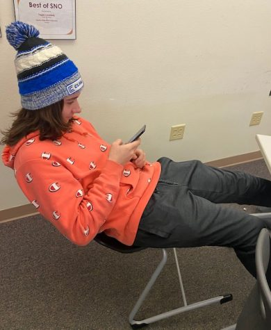 "PHS senior Tristan Willett leans back in his chair and plays on his phone while wearing his beanie, which is against the school's dress code. He's one of many high school students who haven't been able to shake the ""mid-semester slump"" since the third grade."