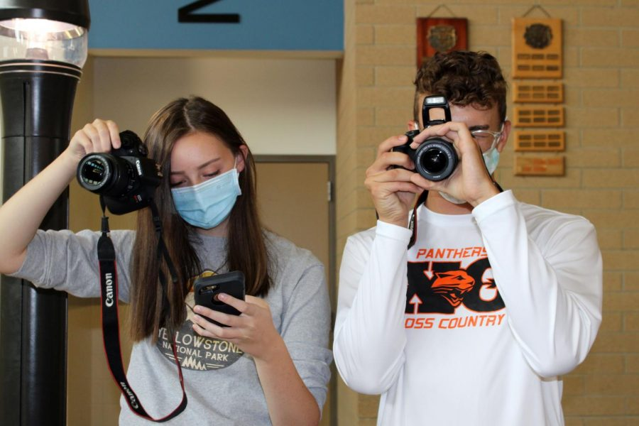 PHS Prowl Editor-in-Chief Abigail Landwehr and Opinion Editor Ben Whitlock hold up cameras. Landwehr was teaching the staff how to use and take photos with the digital cameras.