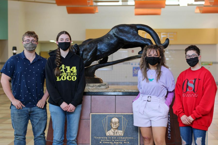 The three Trustees' scholarship recipients (from left) CJ Brown, Jenna Merritt and Elsie Spomer and STARR scholarship recipient Maggie Cappiello pose by the panther statue at the front entrance of the school.