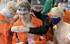 Junior Nate Johnston is congratulated by his teammates at state boys swimming while event winners were announced.
