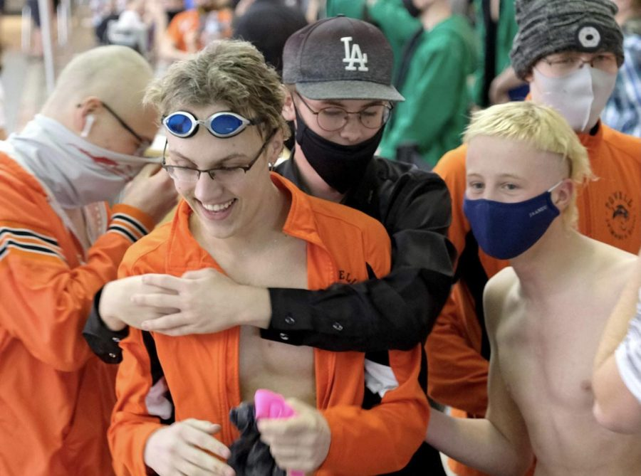 Junior Nate Johnston is congratulated by his teammates at state boys' swimming while event winners were announced.