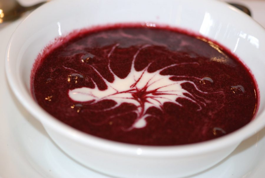 A bowl of blueberry soup is presented with a design made with vanilla yogurt.